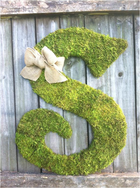 large wood letter s covered in moss