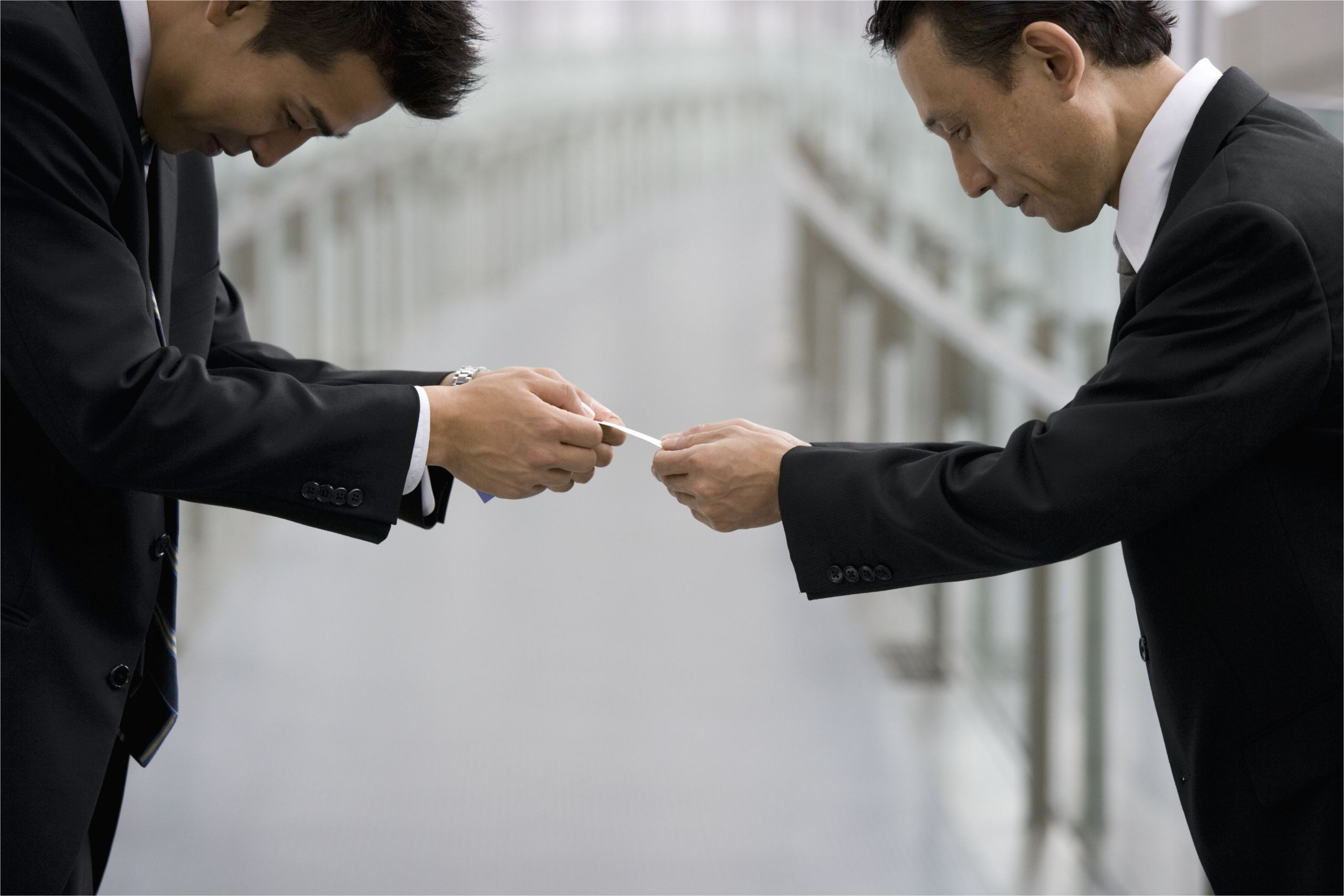 japanese businessmen exchanging business cards 78767477 5c2cd670c9e77c00017e55a9 jpg