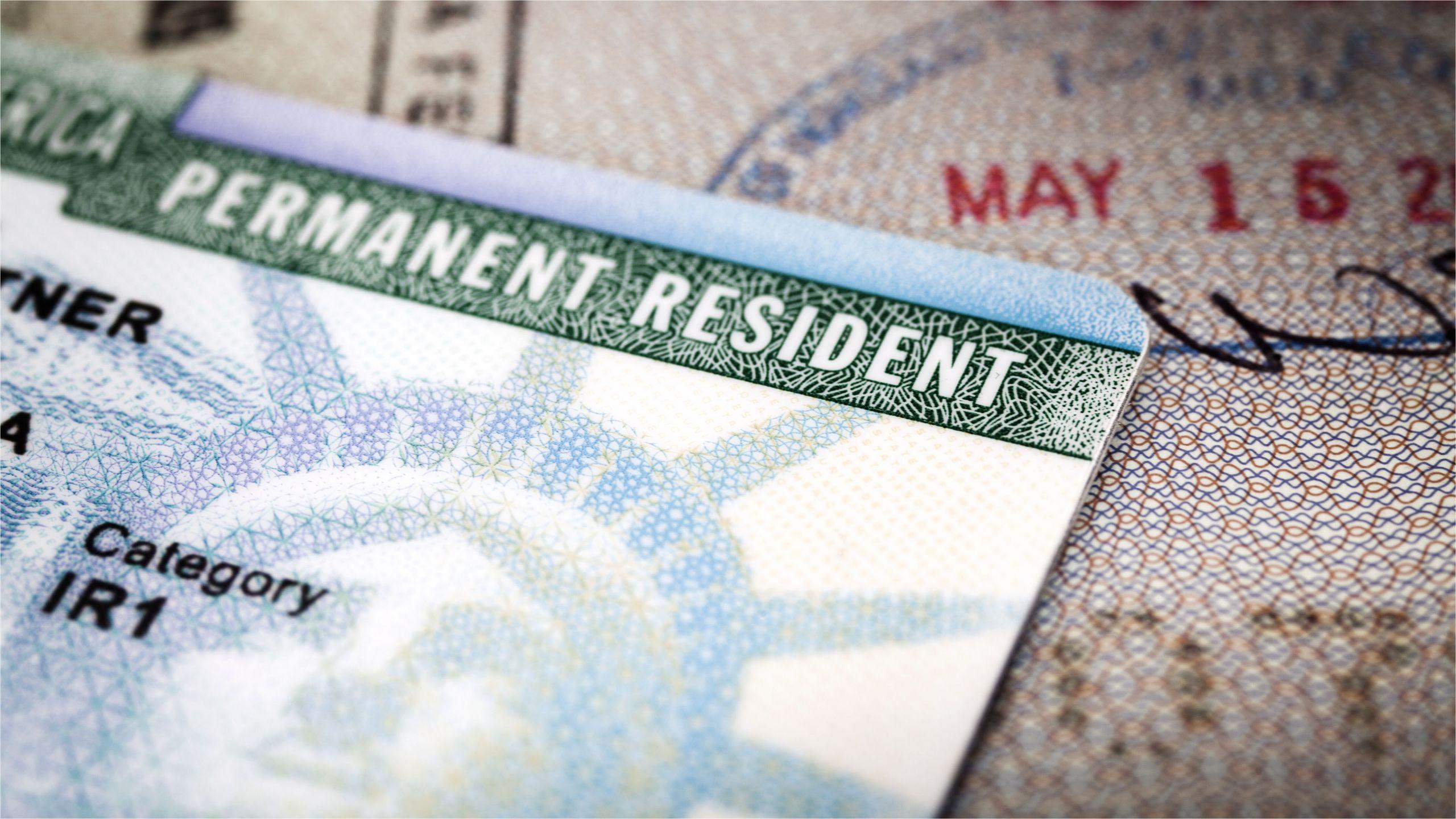 a green card lying on an open passport close up full frame 187591458 5aa6c5caa9d4f900369f3d3d jpg