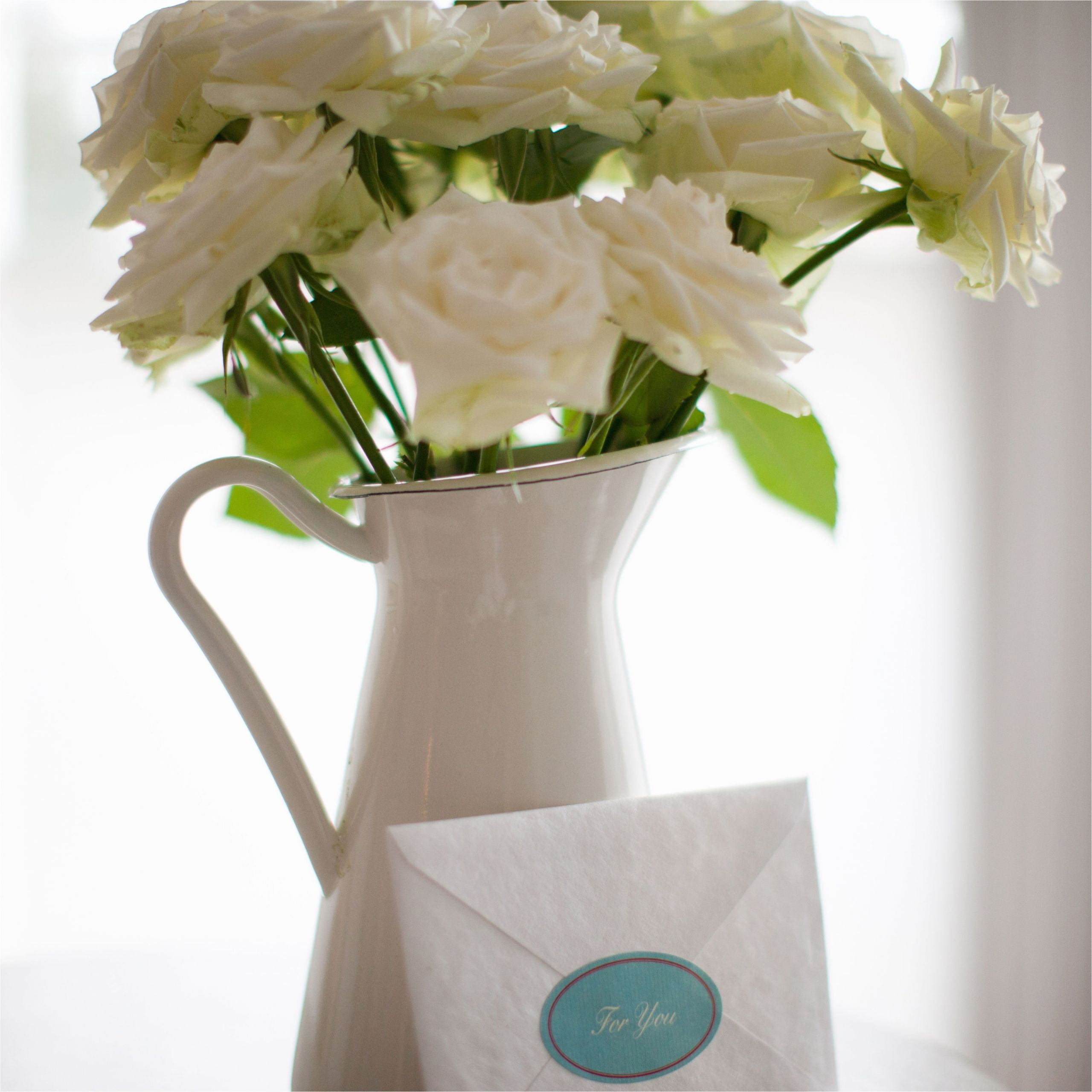 card leaning against white rose bouquet in pitcher 168683856 58d9361e3df78c5162d6ea1b jpg