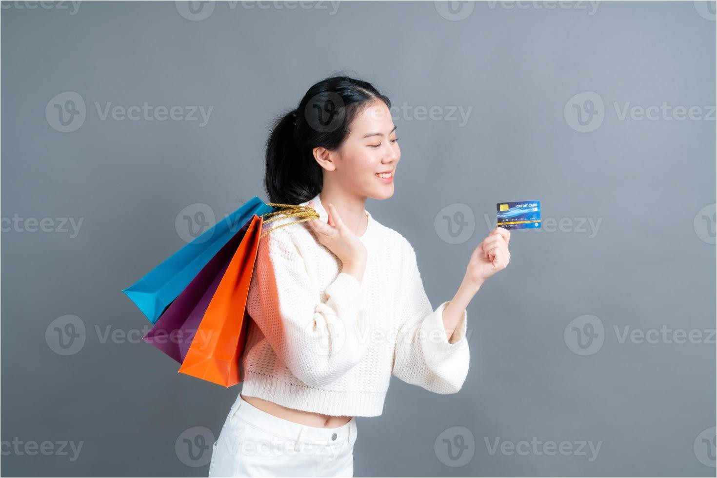 beautiful asian woman with shopping bags and showing credit card