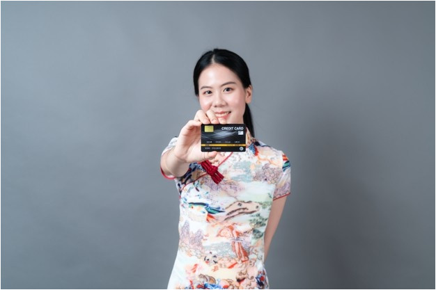 beautiful young asian woman wear chinese traditional dress with hand holding credit card grey background
